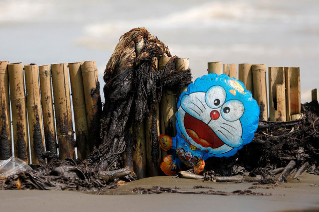 A Doraemon balloon stranded on a bamboo fence is pictured at a beach affected by oil spill in Karawang, West Java province, Indonesia, August 9, 2019. (Photo by Willy Kurniawan/Reuters)