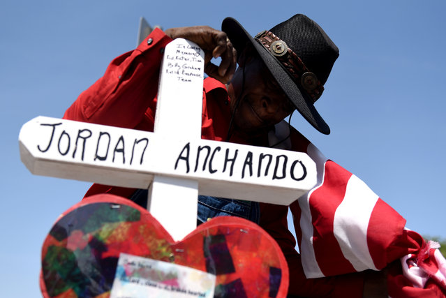 Curtis Reliford knells next to a cross in honor of one of the victims at a growing memorial site two days after a mass shooting at a Walmart store in El Paso, Texas, U.S. August 5, 2019. (Photo by Callaghan O'Hare/Reuters)