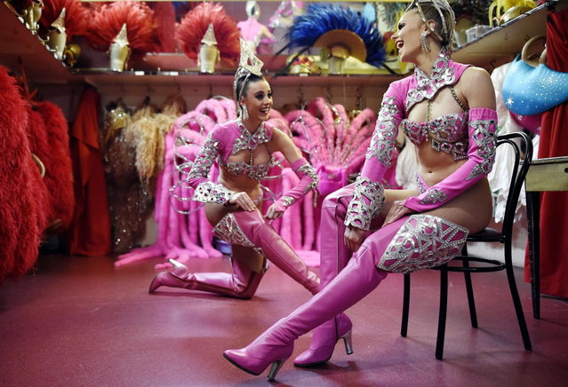 "Dancers of the Moulin Rouge cabaret adjust their boots prior to a show on April 22, 2014 in Paris. Since 1945, the ""Maison Clairvoy"" is specialised in the creation of luxury shoes and started in 1960 a collaboration with the famous Moulin Rouge to create boots and shoes for French Cancan dancers. (Photo by Franck Fife/AFP Photo)"