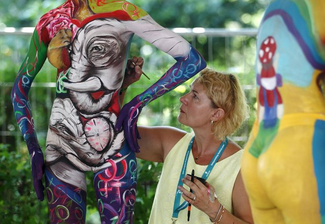 An artist paints a model during the annual World Bodypainting Festival in Poertschach, Austria, July 3, 2015. The event takes place from July 3 to 5 at lake Woerthersee in Austria's southern Carinthia province. (Photo by Heinz-Peter Bader/Reuters)