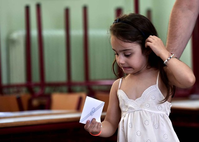 A young girls holds a ballot during the Greek referendum in Athens on July 5, 2015. Greek voters headed to the polls today to vote in a historic, tightly fought referendum on whether to accept worsening austerity in exchange for more bailout funds, in a gamble that could see it crash out of the euro. (Photo by Aris Messinis/AFP Photo)