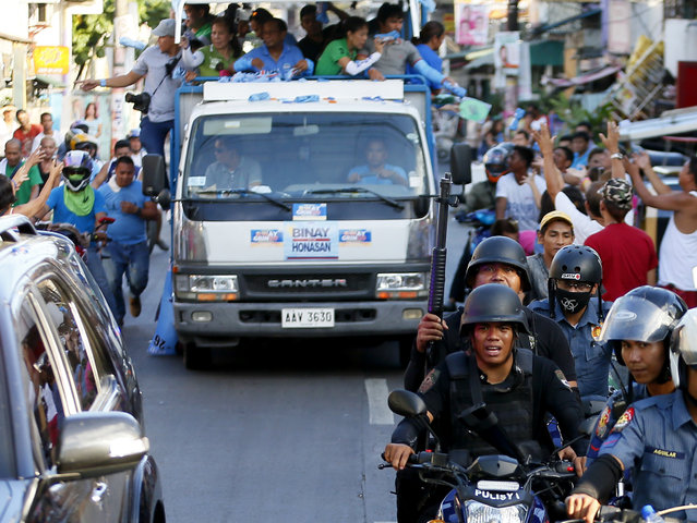 SWAT members of the Philippine National Police provide security to the campaign motorcade of presidential candidate Vice-president Jejomar Binay and congressman Manny Pacquiao, who is running for senator in Monday's national elections during their campaign rally in Navotas north of Manila, Philippines, Friday, May 6, 2016. Boxing star Manny Pacquiao pressed on with his campaign for a seat in the Philippine Senate despite a reported militant plot to kidnap him. (Photo by Bullit Marquez/AP Photo)