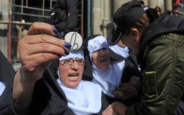 """Members of the """"Mujeres Creando"""" (Women Creating) activist women group dressed as nuns who were protesting against the upcoming visit of Pope Francis to Bolivia, are taken away by police in front of the Metropolitan Cathedral in La Paz, on July 6, 2015.  Pope Francis, in South America on a three-nation tour, will perform mass in Ecuador Monday, with more than a million faithful – many of whom camped out overnight – expected to attend. (Photo by Jorge Bernal/AFP Photo)"""