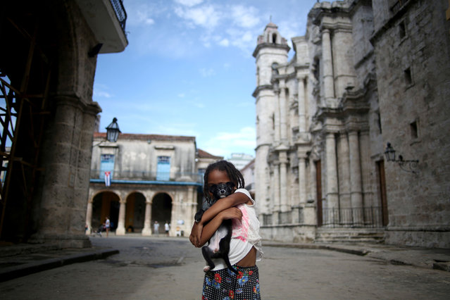 A little girl poses for a picture with her dog outside the Cathedral of Havana, in Havana, Cuba on July 26, 2019. (Photo by Fernando Medina/Reuters)
