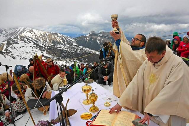 Catholic priests hold a mass during the canonization of Pope John Paul II and Pope John XXIII in Kasprowy Wierch, in Poland's Tatra mountains, on April 27, 2014. Pope Francis proclaimed his predecessors John XXIII and John Paul II saints on Sunday, hailing both as courageous men who withstood the tragedies of the 20th century. (Photo by Marek Podmokly/Agencja Gazeta via Reuters)