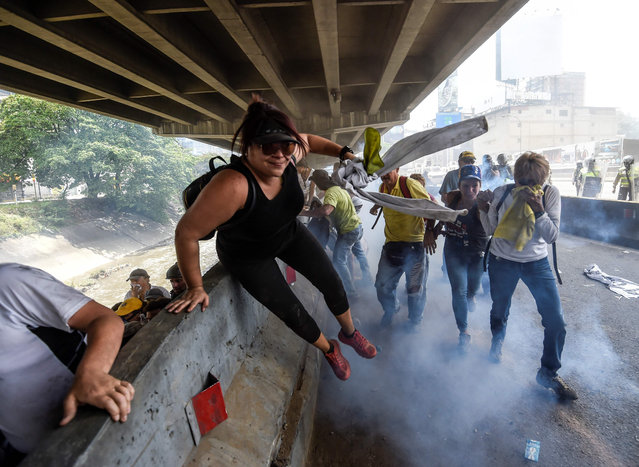 Demonstrators protest during a rally against Venezuelan President Nicolas Maduro, in Caracas on April 19, 2017. Venezuela braced for rival demonstrations Wednesday for and against President Nicolas Maduro, whose push to tighten his grip on power has triggered waves of deadly unrest that have escalated the country' s political and economic crisis. (Photo by Juan Barreto/AFP Photo)