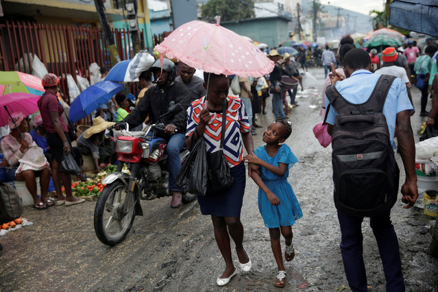 A woman and a girl walk while holding an umbrella after a storm as they walk along a street in Port-au-Prince, Haiti, May 28, 2019. (Photo by Andres Martinez Casares/Reuters)