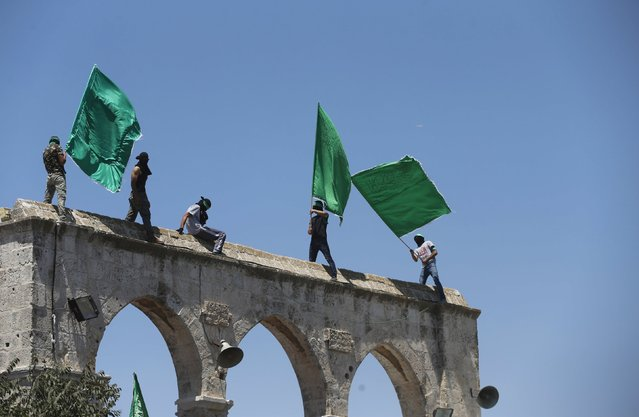 Hamas supporters wave the movement's flag during a rally marking the annual al-Quds Day, or Jerusalem Day, on the fourth Friday of the holy month of Ramadan, at the compound known to Muslims as the Noble Sanctuary and to Jews as Temple Mount, in Jerusalem's Old City July 10, 2015. (Photo by Ammar Awad/Reuters)