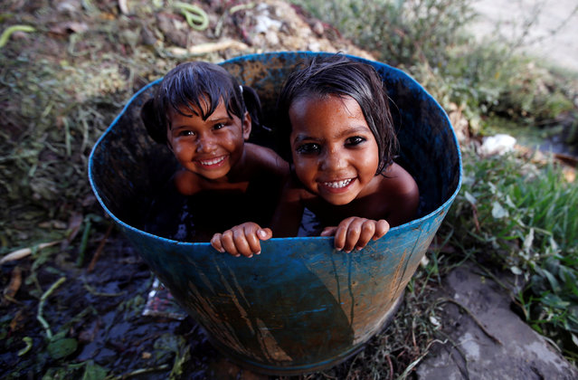 Girls bath inside a drum on a hot summer day at a field in New Delhi, April 18, 2017. (Photo by Adnan Abidi/Reuters)