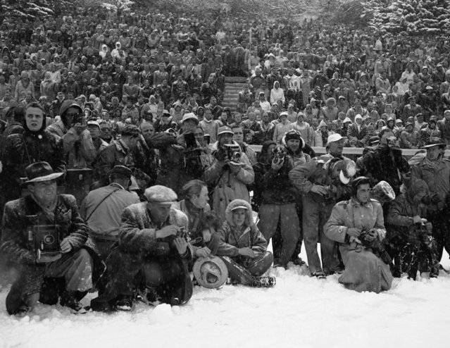 A battalion of photographers wrapped up in diverse costumes during a snowy session of the Winter Olympics on the St. Moritz ice stadium, February 6, 1948, St. Moritz, Switzerland. (Photo by AP Photo/Green)