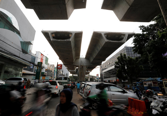 A woman walks across the street under a flyover construction in Jakarta, Indonesia, May 11, 2016. (Photo by Reuters/Beawiharta)