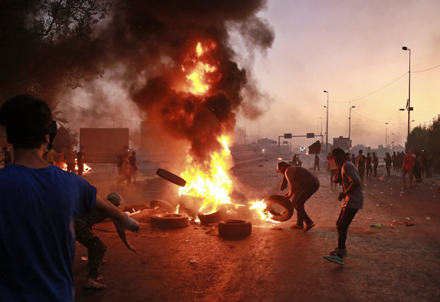 Iraqi security forces fire tear gas while Anti-government protesters set fires and close a street during a demonstration in Baghdad, Iraq, Saturday, October 5, 2019. The spontaneous protests which started Tuesday in Baghdad and southern cities were sparked by endemic corruption and lack of jobs. Security responded with a harsh crackdown, leaving more than 70 killed. (Photo by Hadi Mizban/AP Photo)