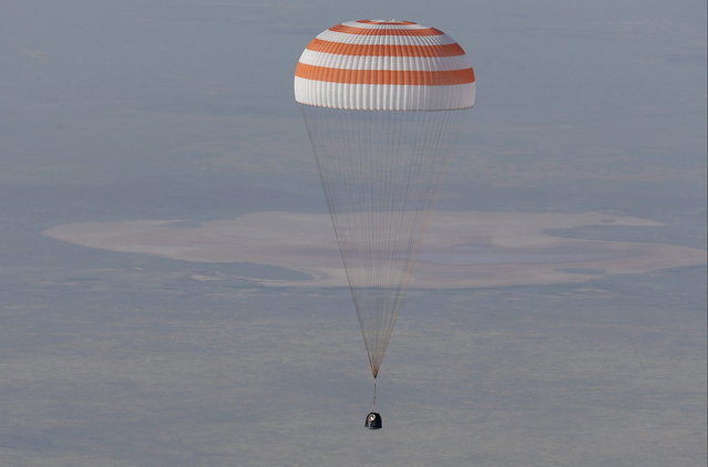 The Soyuz TMA-11M capsule with the International Space Station (ISS) crew members Japanese astronaut Koichi Wakata, Russian cosmonaut Mikhail Tyurin and U.S. astronaut Rick Mastracchio descends beneath a parachute just before landing south-east of the town of Dzhezkazgan in central Kazakhstan, May 14, 2014. The first Japanese to command a space mission and crewmates from the United States and Russia landed safely in Kazakhstan on Wednesday, wrapping up a 188-day stay aboard the International Space Station. (Photo by Dmitry Lovetsky/Reuters)