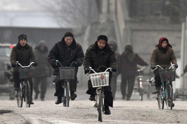 North Koreans ride bicycles at the banks of the Yalu River near the North Korean town of Sinuiju, opposite the Chinese border city of Dandong, December 18, 2013. (Photo by Jacky Chen/Reuters)