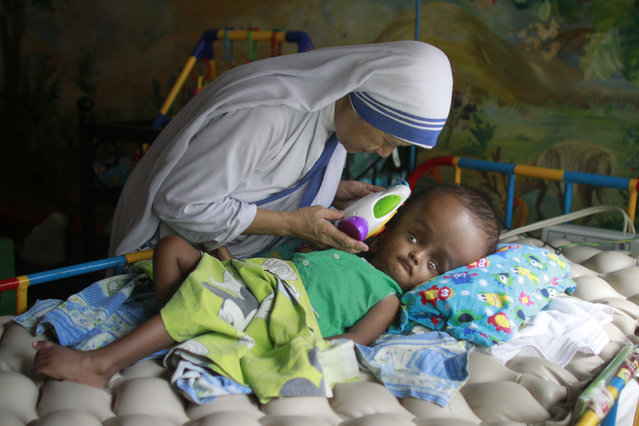 Sister Maricor, from the Missionaries of Charity, spends a moment with one-year-old John, who has hydrocephalus, at an orphanage in Old Dhaka May 11, 2014. (Photo by Andrew Biraj/Reuters)