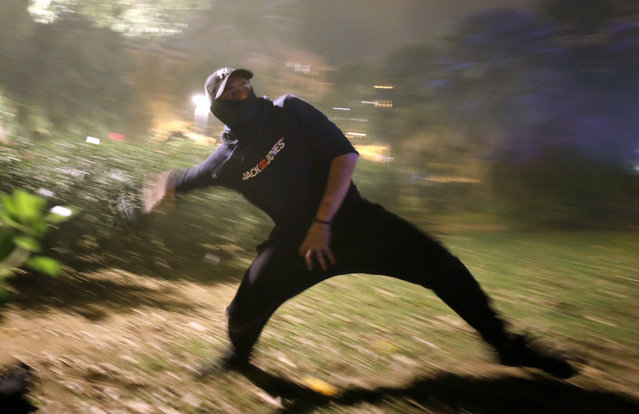 A protestor hurls a rock at police during clashes in Barcelona, Spain, Wednesday, October 16, 2019. Spain's government said Wednesday it would do whatever it takes to stamp out violence in Catalonia, where clashes between regional independence supporters and police have injured more than 200 people in two days. (Photo by Emilio Morenatti/AP Photo)