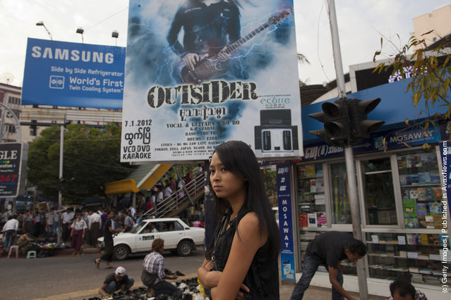 A woman walks past a movie poster  in the central shopping area of the city in Yangon, Myanmar