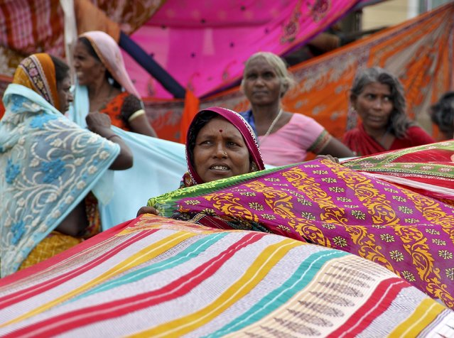 Devotees dry their sarees, a traditional cloth used for women's clothing, after taking a dip in the seawaters of a beach in Odisha, India, July 17, 2015. Devotees are gathering in India's eastern state of Odisha to attend the annual Rath Yatra, or chariot procession that commemorates a journey by Hindu god Jagannath, his brother Balabhadra and sister Subhadra, in specially made chariots. (Photo by Reuters/Stringer)