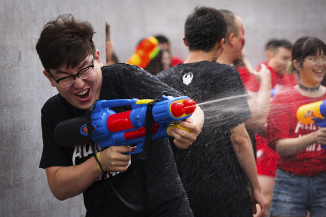 In this Saturday, July 4, 2015 photo, a player fires his water gun as he participates in a battle maze in Beijing. Players, also cooling off from the summer heat, divided into teams of aliens, humans, and zombies to soak each other with water guns in the large outdoor maze, which organizers said was inspired by the online and mobile video games that are increasingly popular with China's youth. (Photo by Mark Schiefelbein/AP Photo)