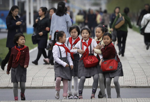 North Korean school girls react upon seeing their photograph being taken as they walk along Mirae Scientists Street on Wednesday, April 19, 2017, in Pyongyang, North Korea. Tensions have spiked in recent weeks over North Korea's advancing nuclear technology and missile arsenal. But in Pyongyang, where war would mean untold horrors, few people seem to care much at all. (Photo by Wong Maye-E/AP Photo)