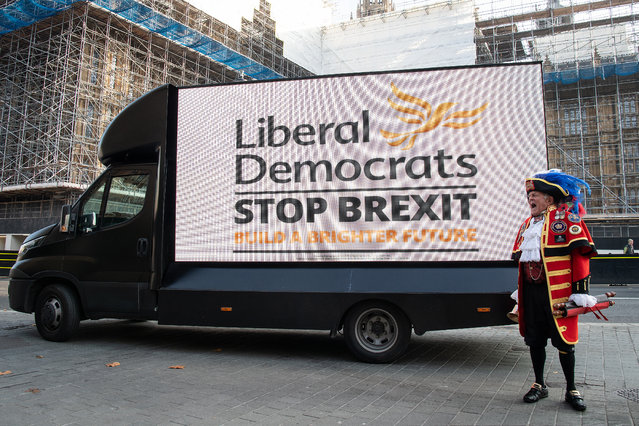 Town crier Tony Appleton stands in front of a digital screen as it displays the new Liberal Democrat election campaign slogan on the back of a van outside the Houses of Parliament at Old Palace Yard on October 31, 2019 in London, England. (Photo by Leon Neal/Getty Images)