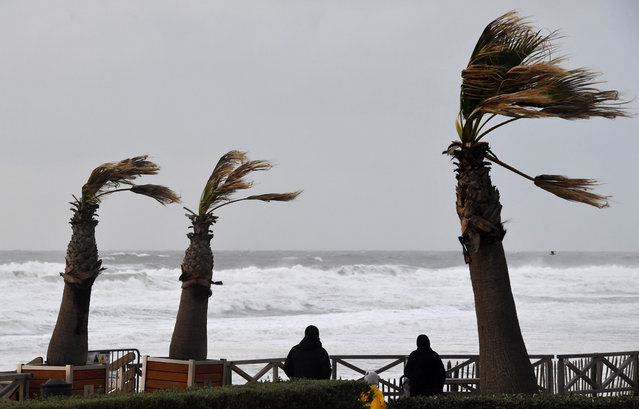 People walk on the waterfront of Lacanau, southwestern France, on November 3, 2019, after the storm Amelie. Some 100,000 households were deprived of electricity on the morning of November 3, 2019 in south western France, where the Atlantic coast was swept by storm Amelie, causing damage but no casualties, according to an initial assessment by the emergency services and the prefectures (Photo by Mehdi Fedouach/AFP Photo)