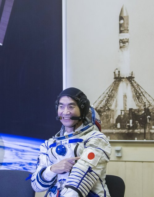 The International Space Station (ISS) crew member Kimiya Yui of Japan points to his national flag after donning his space suit at the Baikonur cosmodrome, Kazakhstan, July 22, 2015. (Photo by Shamil Zhumatov/Reuters)