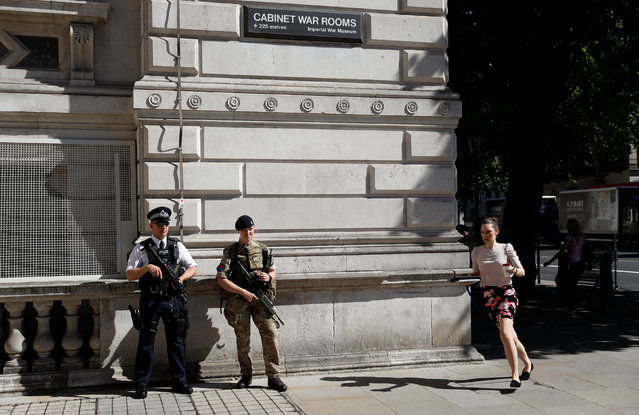 A woman rushes past a soldier and an armed police officer on duty on Whitehall in London, Britain, May 26, 2017. (Photo by Peter Nicholls/Reuters)