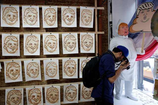 A man photographs artwork referencing U.S. Republican presidential candidate Donald Trump made by the artist Hanksy and being sold at a temporary store in New York, U.S., June 4, 2016. (Photo by Lucas Jackson/Reuters)