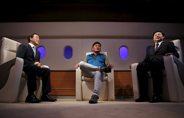 A man sits between the wax figures of U.N. Secretary-General Ban Ki-moon (L) and Chinese President Xi Jinping (R) at Grevin Wax Museum in central Seoul, South Korea, July 30, 2015. (Photo by Kim Hong-Ji/Reuters)