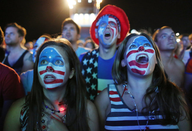 Fans with their faces painted with the U.S. national soccer team's colors, watch a live telecast of the group G World Cup match between United States and Portugal, inside the FIFA Fan Fest area on Copacabana beach, in Rio de Janeiro, Brazil, Sunday, June 22, 2014. (Photo by Leo Correa/AP Photo)