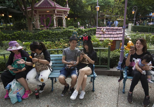 Tourists take a break at Hong Kong Disneyland, in Hong Kong, China, 27 May 2017. The numbers of tourists visiting Hong Kong Disneyland has declined since Shanghai Disneyland opened in June 2016. Shanghai Disney Resort has announced on 19 May that more than 10 million people have visited the park after eleven months of operations, outshining its Hong Kong counterpart which has posted financial losses for two consecutive years. (Photo by Alex Hofford/EFE/EPA)
