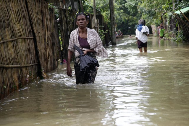 Local residents wade through a flooded road in Bago, 80 kilometers (50 miles) northeast of Yangon, Myanmar, Saturday, August 1, 2015. (Photo by Khin Maung Win/AP Photo)