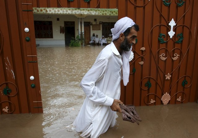 A man walks through floodwater after heavy rainfall caused flooding in Peshawar, Pakistan, July 26, 2015. (Photo by Khuram Parvez/Reuters)