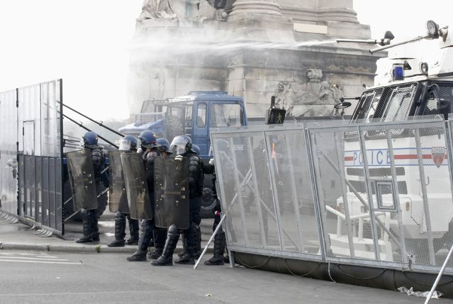 French gendarmes and CRS riot police stand next to water canon vehicules during clashes with demonstrators at the Invalides square during a demonstration in Paris as part of nationwide protests against plans to reform French labour laws, France, June 14, 2016. (Photo by Jacky Naegelen/Reuters)