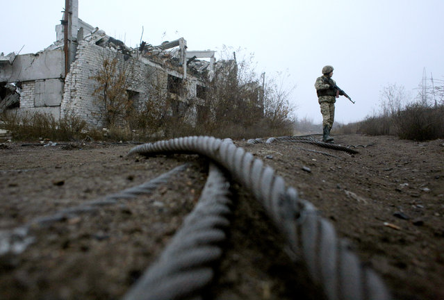 "A Ukrainian serviceman patrols by a destroyed coal mine of Butovka at the front line with Russia-backed separatists not far from the town of Avdiivka, Donetsk region on November 7, 2019. Ukraine's army and Kremlin-backed separatists on November 8, 2019 postponed the planned pullback of troops in the war-torn east by 24 hours, international monitors said. ""The withdrawal of forces and hardware will start on Saturday, 9 November 2019, at 12:00"" Kiev time (1000 GMT), Martin Sajdik, an Organization for Security and Co-operation in Europe (OSCE) envoy, said in a statement. (Photo by Anatolii Stepanov/AFP Photo)"
