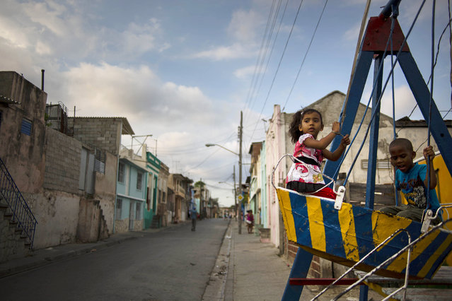 In this March 21, 2015 photo, children play on a swing in Santiago, Cuba. The playground was set up for a youth fair in their neighborhood, and will later be moved to other areas of the city. (Photo by Ramon Espinosa/AP Photo)