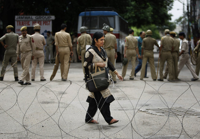 An Indian woman walks near a barbed wire set up as a road blockade by Indian police during a shutdown in Jammu, India, Saturday, August 1, 2015. Protesters on Saturday clashed with policemen on the second consecutive day of a three-day shutdown over the demand for the establishment of All India Institute of Medical Sciences or AIIMS in the region. (Photo by Channi Anand/AP Photo)