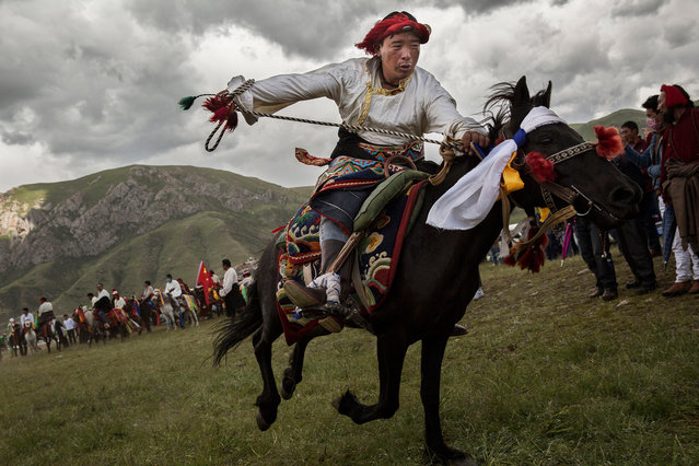 """An ethnic Tibetan nomad performs skills during a riding competition at a local festival on July 26, 2015 on the Tibetan Plateau in Yushu County, Qinghai, China. Tibetan nomads face many challenges to their traditional way of life including political pressures, forced resettlement by China's government, climate change and rapid modernization. The Tibetan Plateau, often called """"The Roof of the World"""", is the world's highest and largest plateau. (Photo by Kevin Frayer/Getty Images)"""