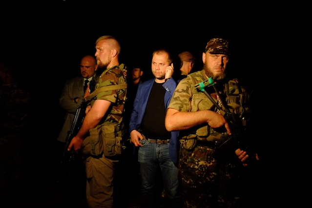 """Self-proclaimed Prime Minister of the pro-Russian separatist """"Donetsk People's Republic"""" Alexander Borodai (C) stands as he arrives on the site of the crash of a malaysian airliner carrying 298 people from Amsterdam to Kuala Lumpur, near the town of Shaktarsk, in rebel-held east Ukraine, on July 17, 2014. The plane was shot down over Ukraine by a surface-to-air missile Thursday but it was unclear who fired the weapon, US officials said. (Photo by Dominique Faget/AFP Photo)"""