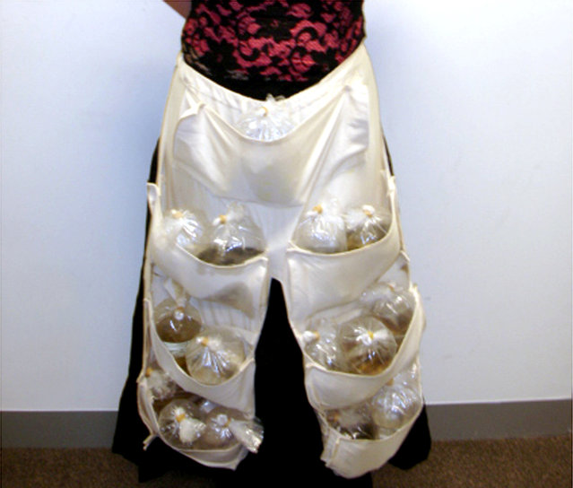 """A woman on a flight from Singapore to Melbourne shows the 51 live tropical fish hidden in a specially designed apron under her skirt in this handout photograph from the Australian Customs Service on June 3, 2005. Customs officers became suspicious after hearing """"flipping"""" noises coming from the vicinity of her waist, and an examination revealed 15 plastic water-filled bags holding concealed fish. (Photo by Reuters/Australian Customs Service)"""