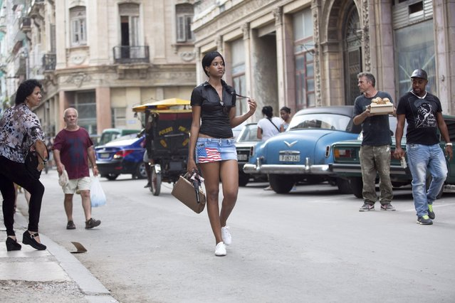 Aylen Hernandez (C), 23, walks in downtown Havana, July 21, 2015. (Photo by Alexandre Meneghini/Reuters)