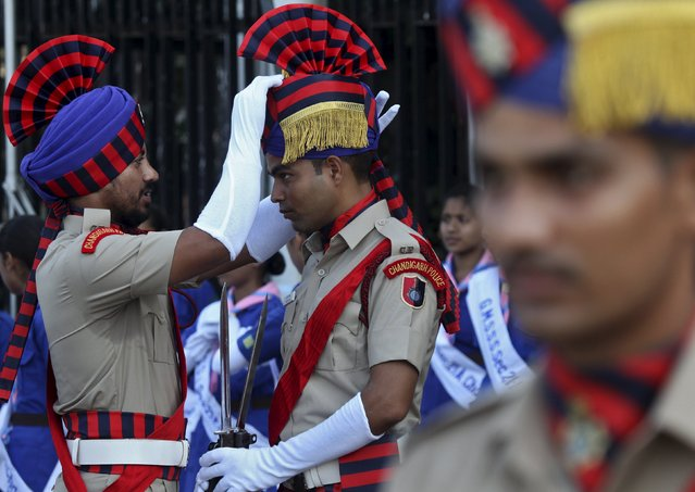 An Indian policeman adjusts his colleague's headdress during the full-dress rehearsal for India's Independence Day celebrations in Chandigarh, India, August 13, 2015. (Photo by Ajay Verma/Reuters)