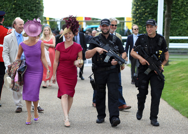 Two racegoers get an armed escort into the Goodwood festival on day one of the Qatar Goodwood Festival at Goodwood racecourse on August 1, 2017 in Chichester, England. (Photo by John Walton/PA Wire)