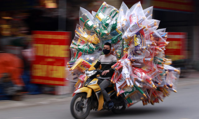 A man rides motorbike loaded with joss paper products for sale in preparation for the Lunar New Year, or Tet holiday in Dao Tu village, in Bac Ninh, Vietnam, 30 December 2019. Vietnamese people often burn joss paper, a papier-mache form of material items such as money, gold, houses, cars during Tet holiday to pray for their ancestors. (Photo by Luong Thai Linh/EPA/EFE)