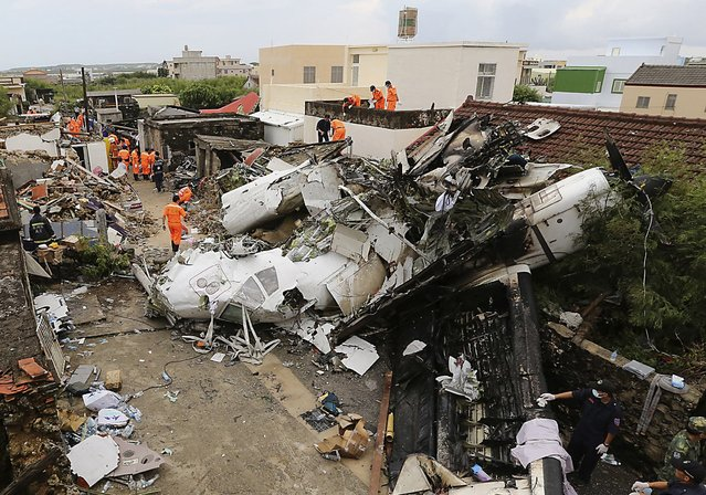 Rescue personnel survey the wreckage of a TransAsia Airways turboprop plane that crashed, on Taiwan's offshore island Penghu July 24, 2014. The leaders of rivals China and Taiwan expressed condolences on Thursday for victims of the plane that crashed during a thunderstorm the previous day killing 48 people including two French nationals. (Photo by Reuters/Stringer)