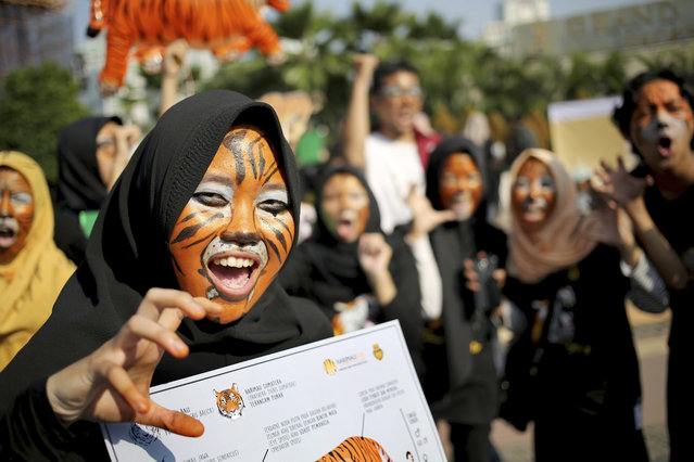 Activists with faces painted to resemble tigers, take part in a rally against Sumatran tiger trade that marks the International Tiger Day, in Jakarta, Indonesia, Sunday, July 30, 2017. (Photo by Tatan Syuflana/AP Photo)