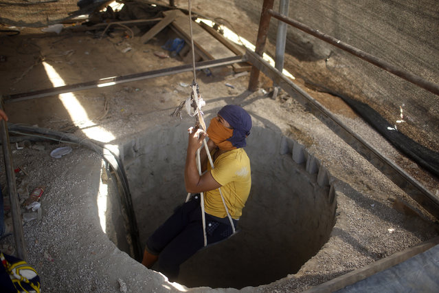 A Palestinian tunnel worker is lowered on a rope into a smuggling tunnel dug beneath the Gaza-Egypt border in the southern Gaza Strip August 26, 2013. (Photo by Mohammed Salem/Reuters)