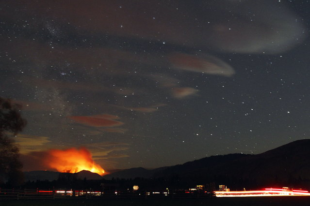 "In this photo taken with a long shutter speed on Thursday night, August 20, 2015, the Black Canyon fire lights up the night sky in Chelan, Wash. Washington Gov. Jay Inslee says his state is facing an ""unprecedented cataclysm"" from the many fires raging across the region. (Photo by Genna Martin/The Herald via AP Photo)"