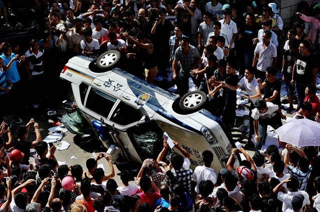 Protesters push over a police vehicle as they gather to demonstrate against plans for a water discharge project in Qidong, China on July 28, 2012. The government in the city announced on its official website Saturday that the plans were scrapped amid the strong opposition by local residents, who are concerned over potential pollution. (Photo by Kyodo News)
